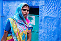 India, Jodhpur, Blue City, Historical City, Rajasthani woman walking in front of blue house