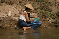 Woman washing veggies in the Nam Khan or Khan River in Luang Prabang, Laos. Laos has one of the lowest population densities in Asia, even though the total population has more then doubled in the last 30 years.