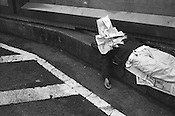 Homeless man sleeping under newspapers, beneath empty billboards, in Shinjuku,. Tokyo, Japan.
