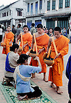 Buddhist novices and monks receiving alms on a street in Luang Prabang, Laos.