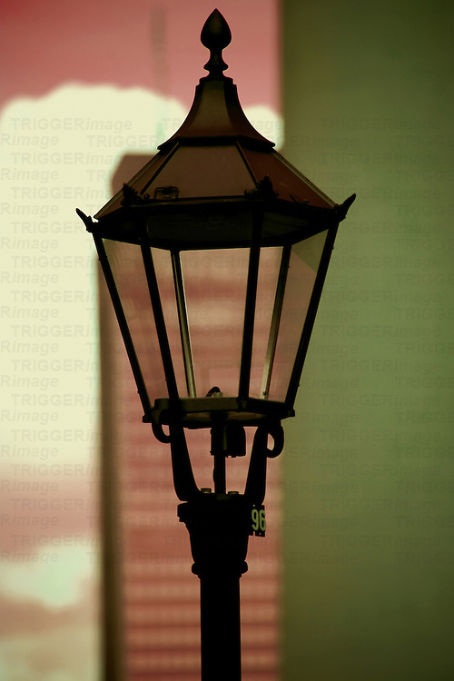 The close-up of a nostalgic lantern with a blurred skyscraper, clouds and a part of the Berlin TV tower in the background.
