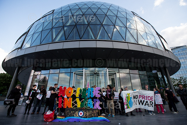 London, 24/05/2016. Today, LGBTQUI (Lesbian, Gay, Bisexual, Transgender, Queer or Questioning, and Intersex) and antimilitarist groups - including Veterans for Peace - held a demonstration and a vigil outside City Hall to protest against the RAF's Red Arrows fly over the Pride in London Parade 2016. From the organisers Facebook page: &lt;&lt;[&hellip;] We represent a cross-section of people from the LGBTQ community and anti-militarist groups who were shocked and outraged by the announcement that the Red Arrows would be flying over London Pride this year. The British military is deeply implicated in a history of homophobic and transphobic oppression, and is responsible for the destruction of human lives, including those of foreign LGBTQ communities, and the social infrastructure that supports them. On a day that commemorates and celebrates the courageous struggles of past and present LGBTQ individuals and communities against oppression and violent prejudice, we find it deeply offensive that the event is providing a platform for the RAF to sanitise its image and divert attention away from its role in executing British military objectives across the world, and the human suffering that such operations involve. We demand the unreserved withdrawal of the invitation of BAE Systems to march on this year&rsquo;s parade, and of the RAF's Red Arrows (which includes BAE-provided aircrafts) to fly over the parade. We call upon all concerned individuals and groups from within and without the LGBTQ community to join us in protesting this attempt to use London Pride as a branding exercise and divert attention away from complicity in war crimes and needless human suffering. Because we take Pride in radically challenging gendered and sexual oppression, not in assimilation to the status quo. Because an injustice to one is an injustice to all. Because there is No Pride in War. [&hellip;]&gt;&gt;.<br />