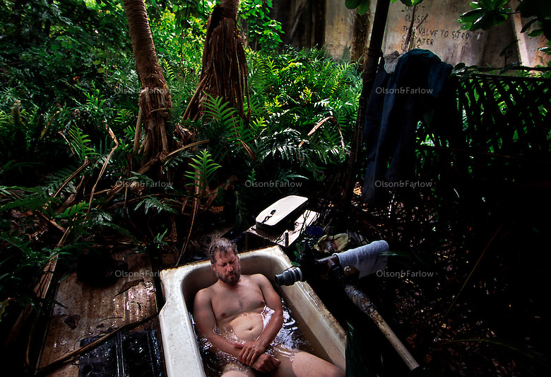 """Dave Johnson came to Palmyra to set up communication equipment.  He takes a daily bath in gerry rigged by yachties to an old military cachement basin.  This tub was used by many characters including the murderer from best selling book """"And the Sea Will Tell.""""The largest purchase to date for the Nature Conservancy is the Palmyra an atoll situated about 300 miles north of the equator.  Palmyra has five times as many coral species as the Florida Keys and three times as many as Hawaii.  It is home to the world's largest invertebrate, the rare coconut crab, and a population of red-footed booby birds second only to that of the Galapagos.  It is the last marine wilderness area left in the U.S. tropics and is home to the last remaining stands of Pisonia grandis beach forest in the world.  Palmyra was a US Navy supply base in World War II, the site of a proposed nuclear waste dump, an unsuccessful coconut plantation and of various development schemes.  Palmyra is most famous for the 1974 slaying  of a married couple which became the subject of the best-selling book """"And the Sea Will Tell,"""" by Vincent Bugliosi."""