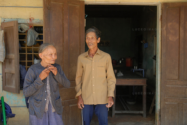 A man and his wife stand outside their home in Hoi An, Vietnam.