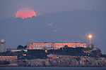January's winter full moon rose over Alcatraz Island as seen from Fort Point San Francisco, CA.