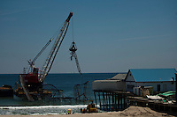 A crane works to remove remnants of the Jet Star roller coaster that had been left in the ocean after Superstorm Sandy hit Seaside Heights last year, in New Jersey  May 14, 2013, Photo by Eduardo Munoz Alvarez / VIEWpress.
