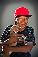 Hasuan Ellis holds his seven-week-old pit bull puppy for a pet portrait.