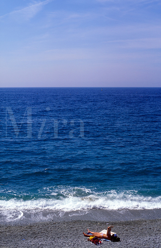 Italy, Cinque Terre, Monterosa. young woman reading newspaper by the sea