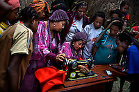 Women in a remote village outside Wamena watch the 'Twin Teachers' Rian and Rossy demonstrate how to use the sewing machine they donated. The trials and tribulations of the twin sisters' crusade has not deterred their passion for work. Instead, they have expanded to various parts of the country promoting training modules to gain practical skills as part of their adult education programme targeting women empowerment. Since the early 1990s, twin sisters Sri Rosyati (known as Rossy) and Sri Irianingsih (known as Rian) have used their family inheritance to set up and run 64 schools in different parts of Indonesia, providing primary education combined with practical skills to some of the country's most deprived children.   .