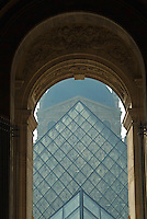 The pyramid of the Musée du Louvre seen through an arched window, Paris, France.