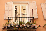 A balcony with white shudders and many painted flower pots in Madrid, Spain. A typical Spanish balcony with a lot of flower pots on it, in Madrid, Spain.