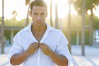 hot man unbuttoning his white shirt while on the beach at sunset in Florida