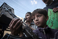A Syrian youth chants anti government slogans as a kid holds a weapon during a demostration after friday prayers in the Bustan Al Qasr district of Aleppo, Syria.