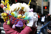 A woman drinks water while people take part during the annual easter parade in Manhattan, New York, 03.27.2016. This annual tradition has been taking place in New York City for over 100 years, Photo by VIEWpress.