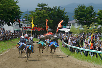 Horse races, Somanomaoi Festival, Minami-soma City, Fukushima Prefecture, Japan, July 28, 2013. During the four-day-long Somanomaoi Festival members of old samurai families ride horseback through the town in traditional armour.  They also take conduct ceremonies at local shrines, take part in horse races, and compete on horseback to catch a flag launched into the air by fireworks.