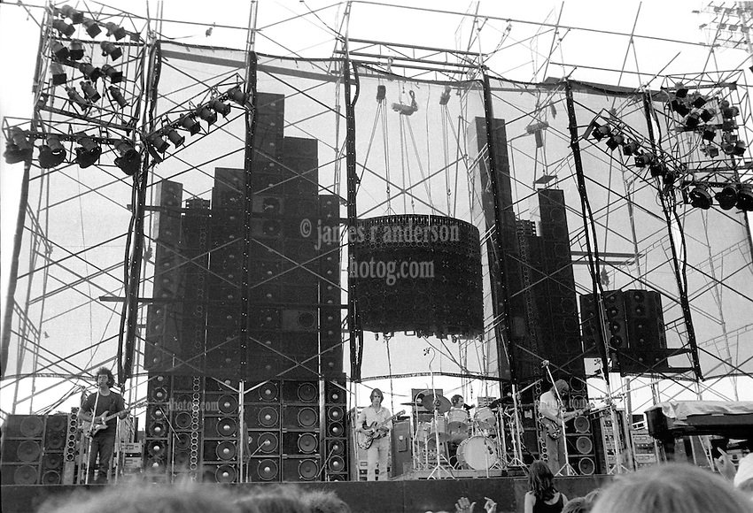 """Grateful Dead with the Wall of Sound in Concert at Dillon Stadium in Hartford CT on the 31st of July 1974. Keith is off to the right out of frame. During the First Set. The hot sun is setting to the left just out of frame. This photo is shot about 75' from the stage showing the entire east coast road tour version of The Wall. Limited Edition Prints only available of this image. No stock sale or publication use of this image available. Only Prints and 16x24"""" is recommended for true impact."""