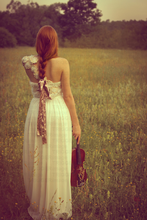 Female youth seen from the back outdoors in spring wearing a white gown and holding a violin.