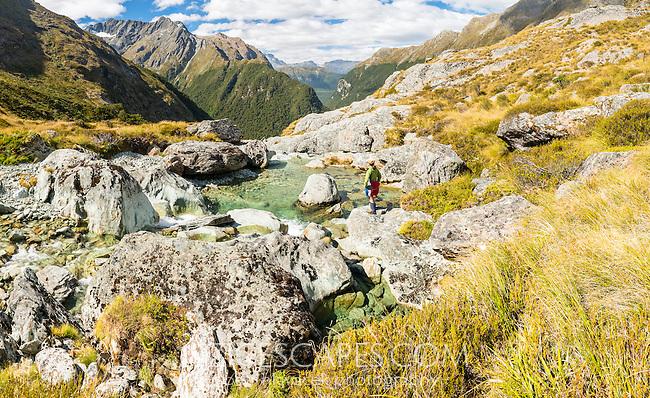Female tramper at stream above Routeburn Falls, Mt. Aspiring National Park, UNESCO World Heritage Area, Central Otago, New Zealand, NZ