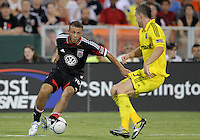 WASHINGTON, DC - AUGUST 4, 2012:  Nick DeLeon (18) of DC United moves the ball away from Josh Williams (3) of the Columbus Crew during an MLS match at RFK Stadium in Washington DC on August 4. United won 1-0.