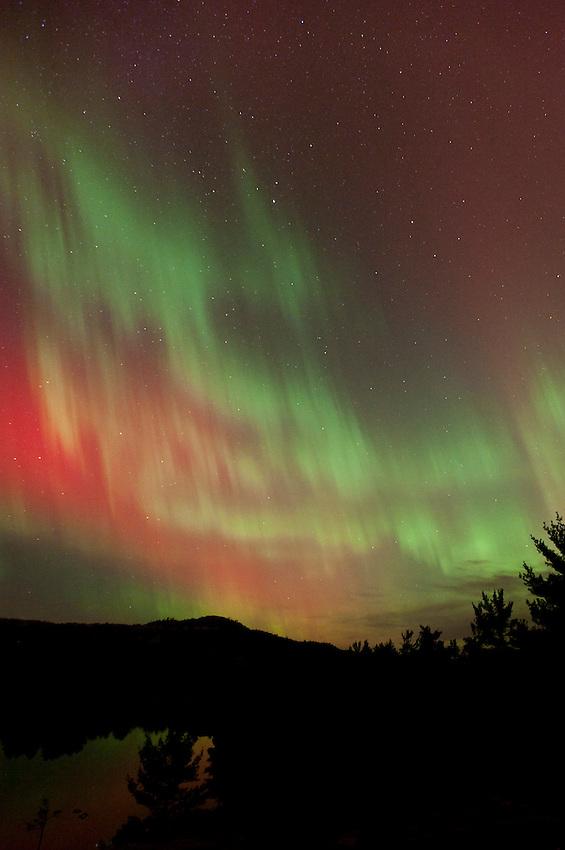 Night mountain bike riding with aurora borealis northern lights near Marquette Michigan.