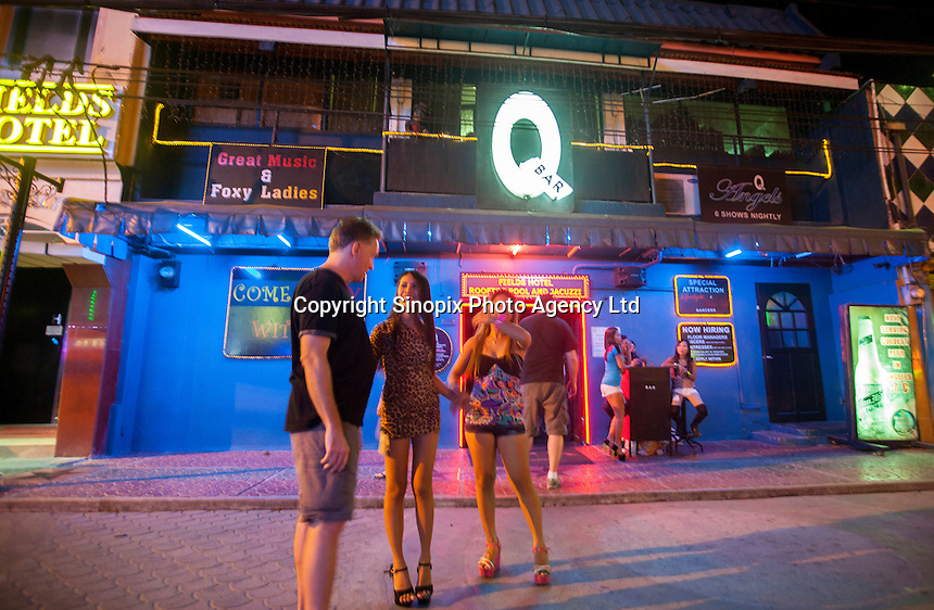 A man chats with prostitutes in front a girly bar on Fields Avenue, the main strip of bars offering cheap prostitutes that runs through Angeles City, Republic of the Philippines, 08 November 2014. The 'sin city', which sprung up on the fringes of a US Air Force base during the Vietnam war, has a reputation for cheap sex, and was a favourite destination for alleged murderer Rurik Jutting, who used to fly to Angeles City from Hong Kong for debauched weekends. The British banker is currently on remand at a secure facility in Hong Kong for allegedly murdering two Indonesian prostitutes in his flat whilst high on alcohol and cocaine.