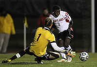 COLLEGE PARK, MD - NOVEMBER 25, 2012: Christiano Francois (3) of the University of Maryland slips the ball past Mark Petrus (1) of Coastal Carolina University during an NCAA championship third round match at Ludwig Field, in College Park, MD, on November 25. Maryland won 5-1.