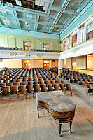 This is a large unused high school auditorium with a high sky-blue ceiling, an empty field of seats, and one lone grand piano in residence waiting for some music lovers to come once again. The school was built in 1917 and the piano was bought new at the time and hasn&rsquo;t moved from the building since. It is in the same rough and dusty condition as the room and balconies it lives in, and is unplayable nowadays with a few missing keys and wobbly wooden legs.<br />