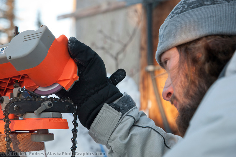 "2009 World Ice Art championships, Fairbanks, Alaska. Multi-block sculpture competition. Sculptor sharpens a chain saw blade for the sculpture ""Stairway to Heaven"" by Buddy Rasmussen; Clay Rasmussen; Robert Childers; Roland de la Garza, USA."