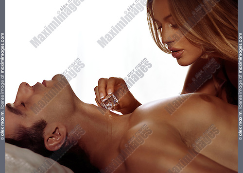 Sensual artistic portrait of a woman touching man's neck with an ice cube