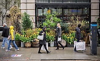 Shoppers walk past a Spring display of tulips and other plants in front of a restaurant in the NoMad neighborhood of New York on Saturday, April 22, 2017.  (© Richard B. Levine)