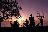 March 26th, 2004-Dili, Timor-Leste-A waiter carries an extra table on his head, as a group of friends enjoy a sunset drink on the beach at a popular seaside bar called Caz Bar in Area Branca just East of Dili.  .Photograph by Daniel J. Groshong/Tayo Photo Group.