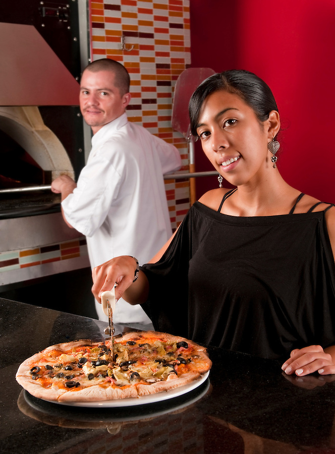 Waitress cutting a pizza while coworker cook works in the oven baking.