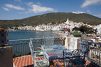 Wrought iron chairs and a glass topped table on a tiled terrace  gives a view of Cadaques, famous for its whitewashed facades of village houses