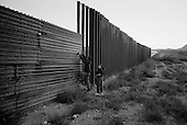 Agua Prieta.Mexico.October 22, 2006..A young Mexican man and woman climb over the border fence to enter the city of Douglas in the USA illegally in the very early morning hours.