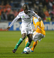 Chicago midfielder Patrick Nyarko (14) dribbles away from Houston midfielder Brad Davis (11).  The Chicago Fire defeated the Houston Dynamo 2-0 at Toyota Park in Bridgeview, IL on April 24, 2010.