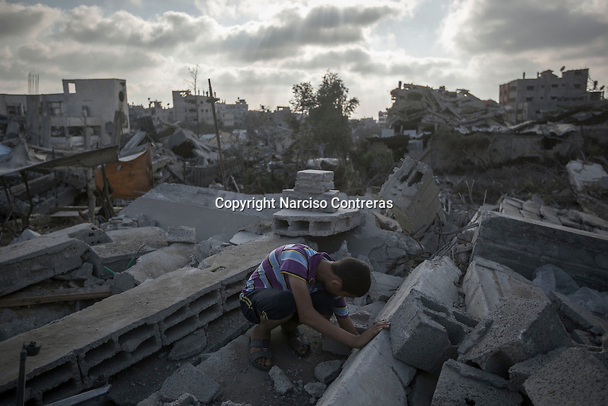 "In this Friday, Aug. 15, 2014 photo, a Palestinian child looks for his belongings among the rubble of his house destroyed by israeli airstrikes and artillery shelling during the ""Protective Edge"" military operation in Shuyaja neighborhood in Gaza City. After a five days truce was declared on 13th August between Hamas and Israel, civilian population went back to what remains from their houses and goods in Gaza Strip. (Photo/Narciso Contreras)"
