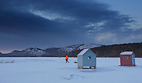 An ice fisherman pulls his sled filled with the day's supplies to his ice fishing shack on Eagle Lake (note the eagle in the sky) in Acadia National Park. It's a typical midwinter morning in downeast Maine with the temperature at 1 degree F and a wind chill of -15F.