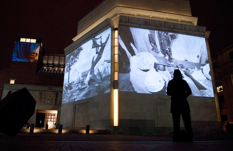 """The U.S. Holocaust Memorial Museum's """"Darfur: Who Will Survive Today?"""" is an exhibit projecting wall-sized images of the escalating genocide in Darfur onto its facade during Thanksgiving week, marking the first time the national memorial's exterior will be used to highlight contemporary genocide. A woman stands outside on Tuesday night, Nov. 21, 2006, taking in the photographs and the accompanying music."""