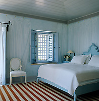 The walls of the main bedroom have been painted with Empire-style trompe l'oeil drapery