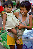 A young boy carrying his sister through the  Manila markets in the Philippines