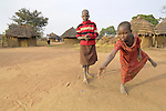 In a camp for families displaced by internal conflict in northern Uganda, Sarah Akellot, age 10 (striped sweater) and Margaret Isiret, age 7, enjoy a game.