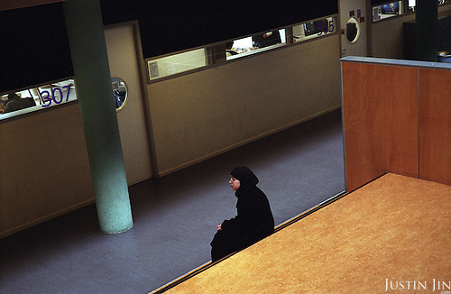 A Dutch Muslim teenager sit on the steps duing break at a vocational school in Amsterdam East..The school is pre-dominantly made up of kids of Turkish, Moroccan and Antillean backgrounds.  .Picture shot in Amsterdam in 2004 by Justin Jin. .