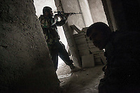In this Friday, Dec. 07, 2012 photo, a Syrian rebel aims toward troops loyal to President Bashar al-Assad during clashes in Aleppo, Syria, Friday. (AP Photo/Narciso Contreras)