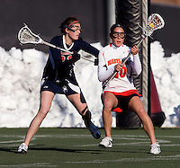 Danielle Kirk (30) of Maryland keeps the ball away from Shannon Cudahy (32) of Richmond at the practice turf field in College Park, Maryland.  Maryland defeated Richmond, 17-7.