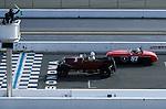 Race cars pass across starting line while starter waves green flag