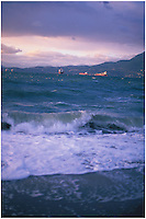 Wave crashing onto Kitsilano Beach with tankers anchored in English Bay waiting to unload cargo in the Port of Vancouver.