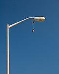 A pair of old tennis shoes hangs from a light fixture over the boardwalk at Rehoboth Beach, Delaware.