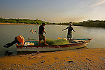 In the early morning, the  two fishermen get their fishing boat  ready for the catch of the day.