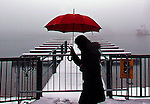 Color meets white as a woman with an umbrella makes her way along the lake while snow from a winter storm falls in Lake Arrowhead Village in Lake Arrowhead Sunday January 06, 2008.