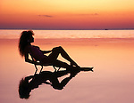 Young woman reclining in calm shallow water  silhouetted by a golden sunset.